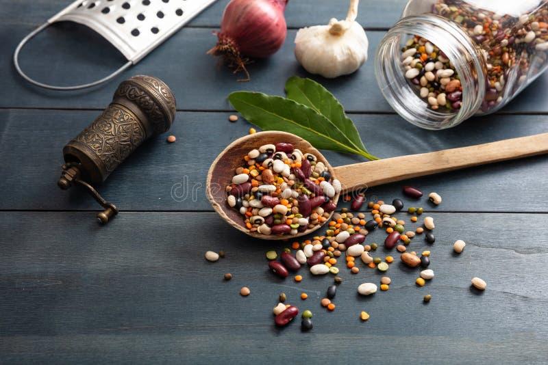 Variedade das leguminosa na concha de madeira, derramada em um fundo do tabletop, em um moedor de pimenta, em uma cebola, em um a imagens de stock