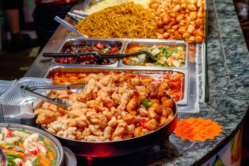 Variedade de alimento chinês cozinhado na exposição para o takeaway no mercado de Camden em Londres imagem de stock