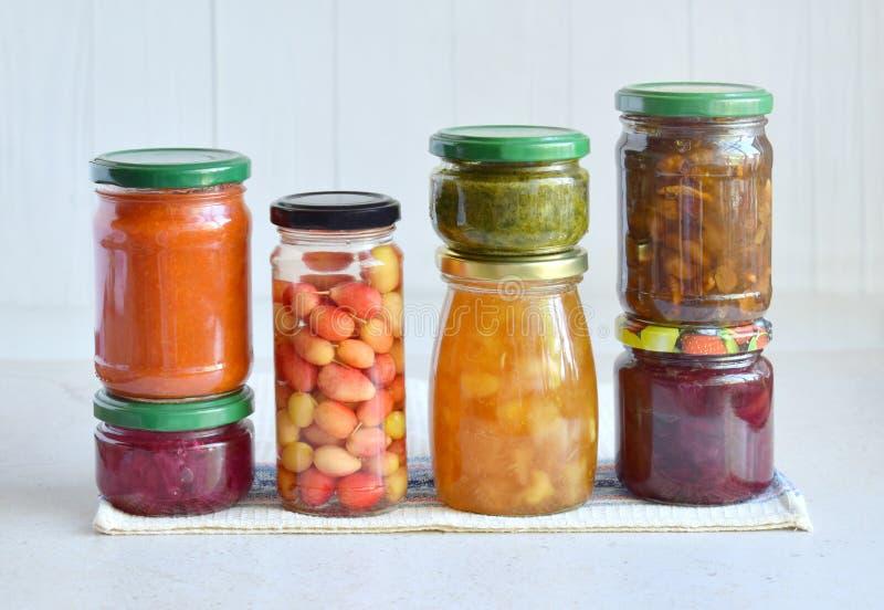 Variedade de alimento preservado nos frascos de vidro - salmouras, doce, doce de fruta, molhos, ketchup Preservando vegetais e fr fotografia de stock