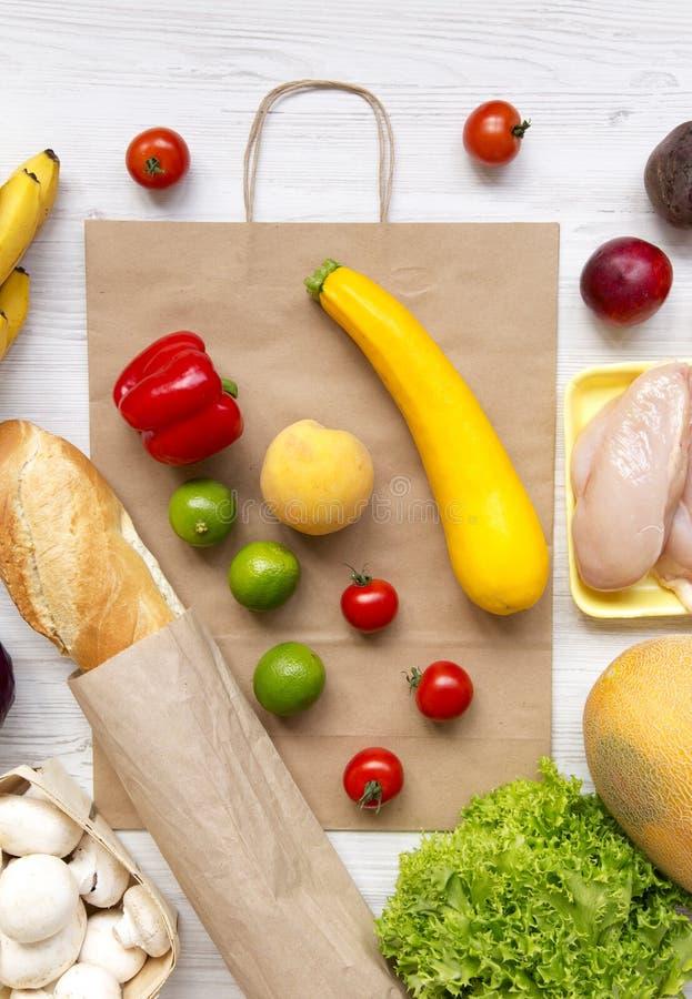 Variedade de alimento saudável com o saco de papel na tabela de madeira branca, aérea Cozinhando o fundo do alimento Frutos fresc fotografia de stock royalty free
