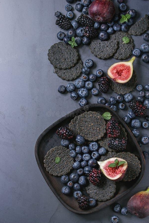 Variedade de bagas e de figos com biscoitos pretos fotografia de stock