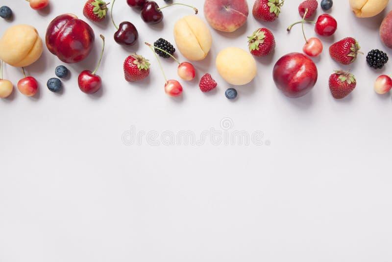 Variedade de bagas e de frutos suculentos frescos no fundo cinzento imagem de stock