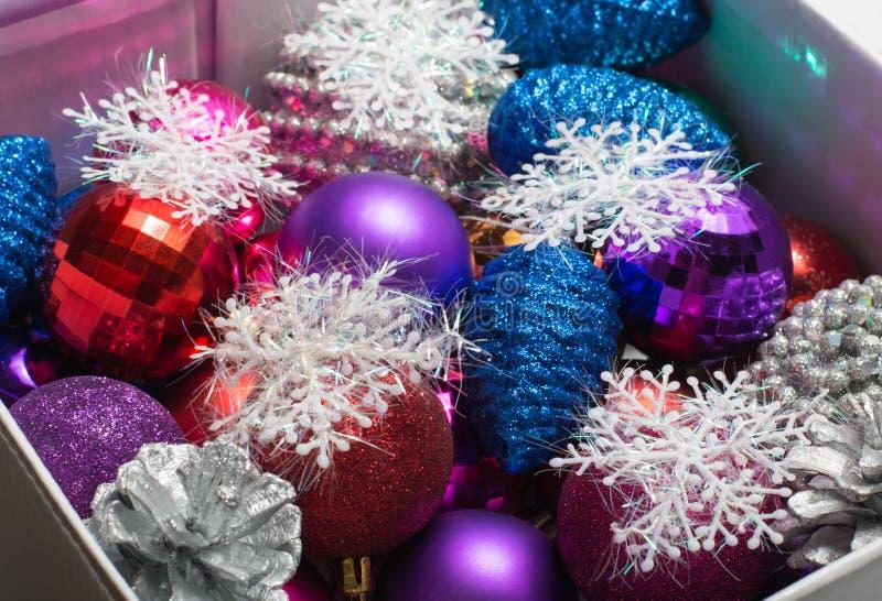 Variedade de bolas do Natal, de cones do pinho e de flocos de neve decorativos em uma caixa imagem de stock