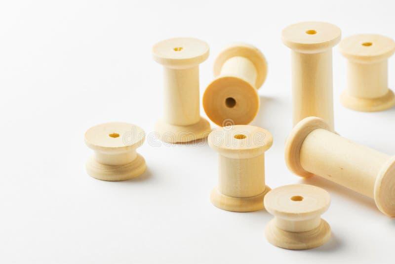 Variedade de carretéis de madeira dos carretéis da linha dos tamanhos diferentes dispersados no fundo branco Costurando os passat imagens de stock