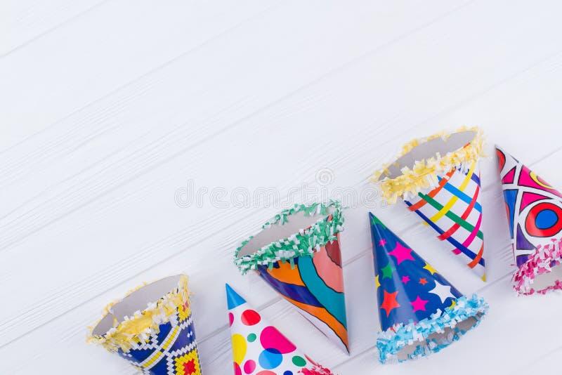 Variedade de chapéus coloridos do partido no fundo de madeira imagem de stock royalty free