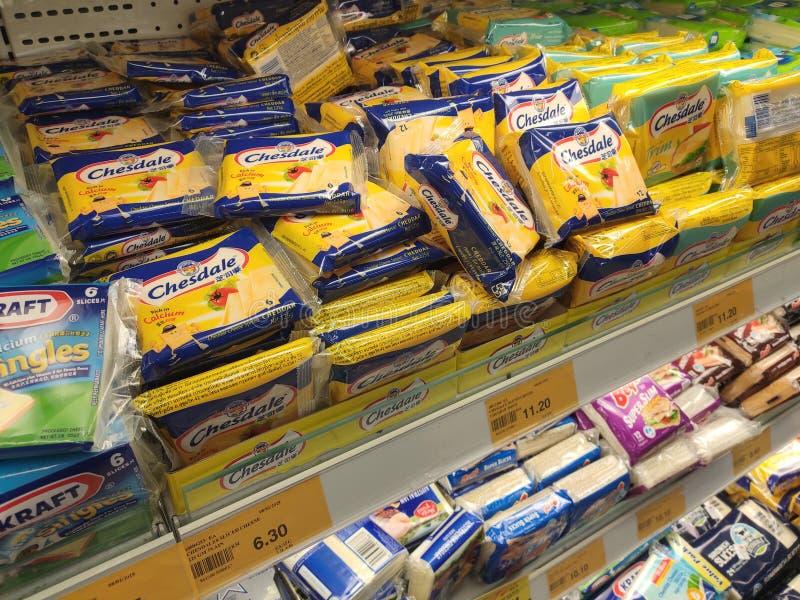 Variedade de fatias embaladas do queijo indicadas na cremalheira do supermercado para a venda fotografia de stock royalty free