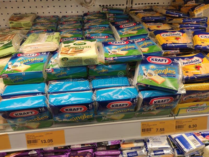Variedade de fatias embaladas do queijo indicadas na cremalheira do supermercado para a venda imagem de stock royalty free