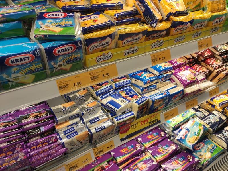 Variedade de fatias embaladas do queijo indicadas na cremalheira do supermercado para a venda foto de stock
