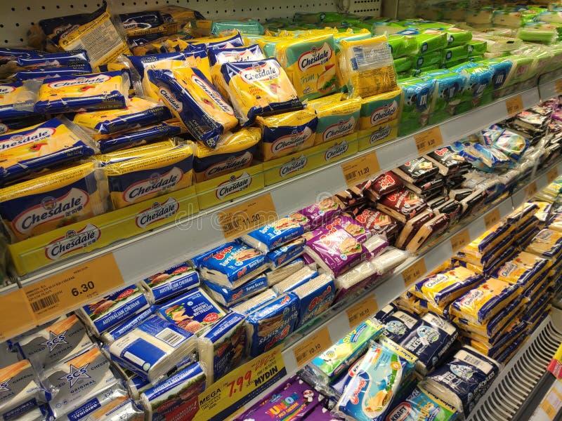 Variedade de fatias embaladas do queijo indicadas na cremalheira do supermercado para a venda imagens de stock