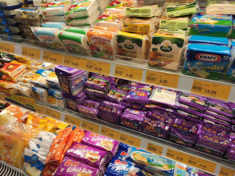 Variedade de fatias embaladas do queijo indicadas na cremalheira do supermercado para a venda imagens de stock royalty free