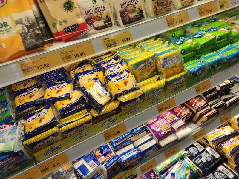 Variedade de fatias embaladas do queijo indicadas na cremalheira do supermercado para a venda imagem de stock