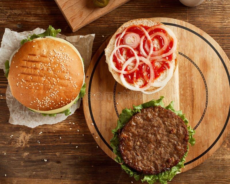 Variedade de hamburgueres, servida na placa de madeira imagens de stock royalty free