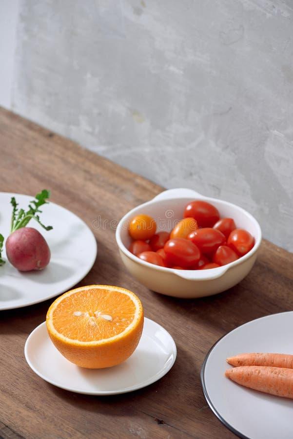 Variedade de ingredientes em um prato, no tomate cinzento da laranja, da cenoura, do rabanete e de ameixa fotos de stock
