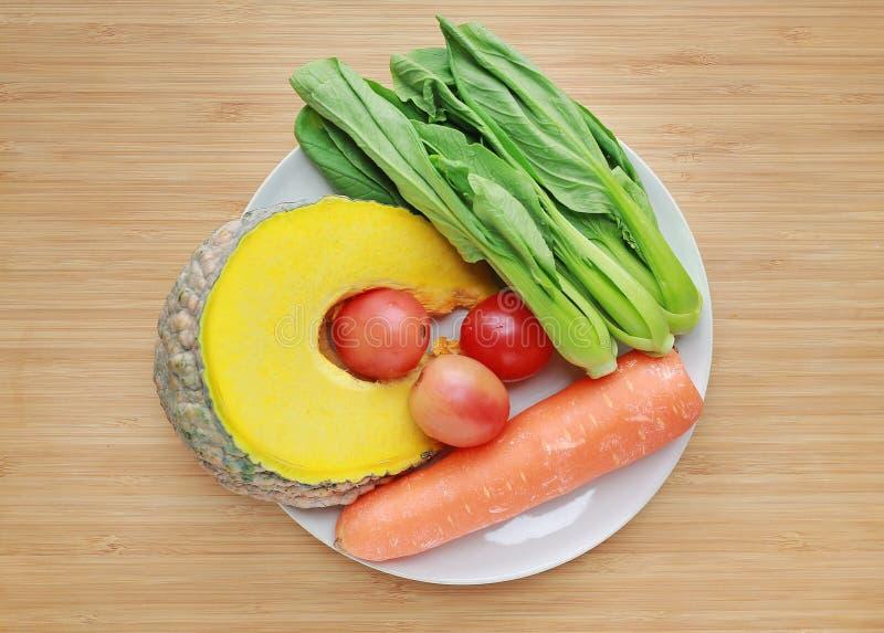 Variedade de legumes frescos na placa branca contra o fundo da placa de madeira foto de stock
