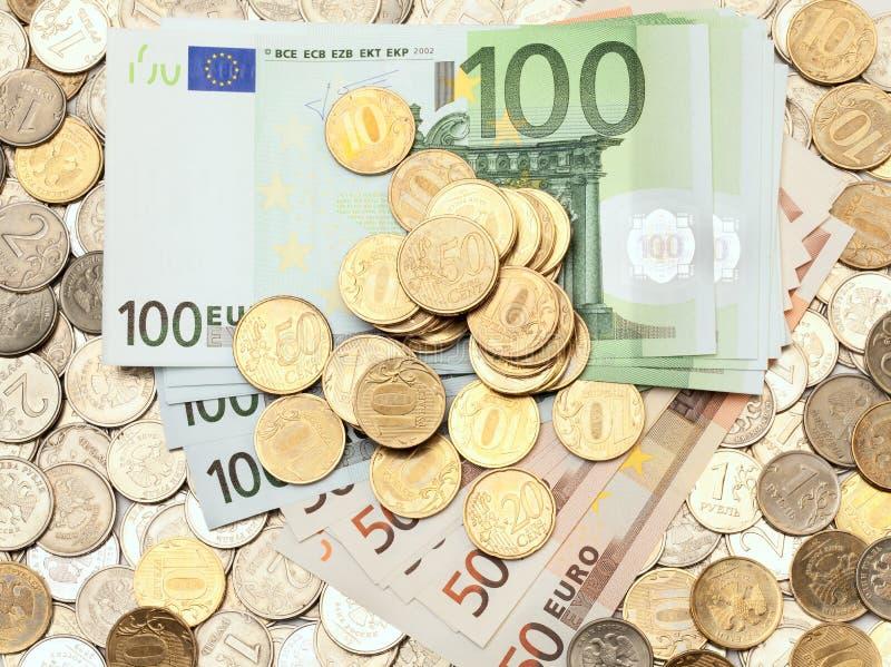 Variedade de moedas e de euro- notas de banco foto de stock