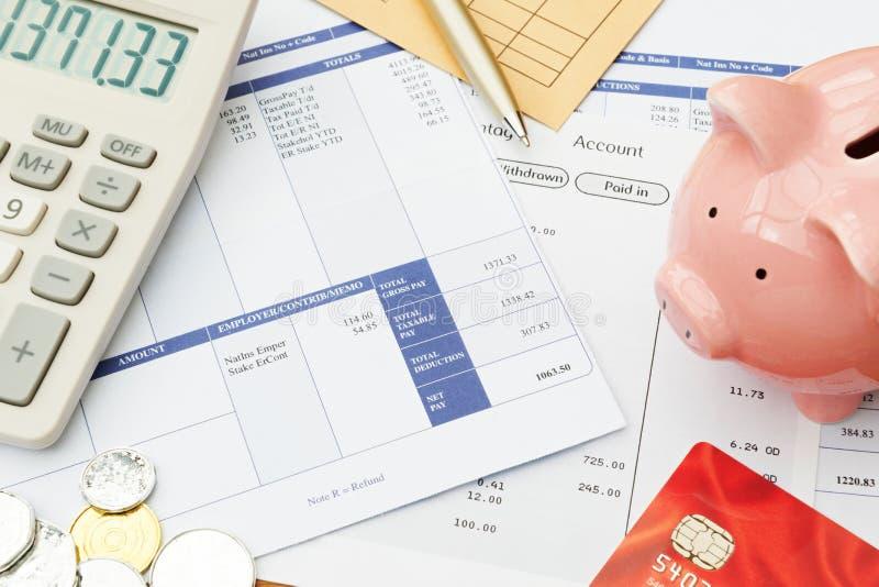 Variedade de objetos financeiros arranjados no deslizamento do salário foto de stock