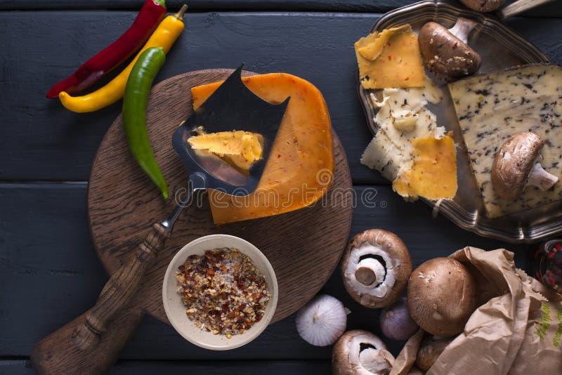 Variedade de queijos em uma placa de madeira Cogumelos, especiarias, pimentas Foto escura ingredientes imagem de stock royalty free