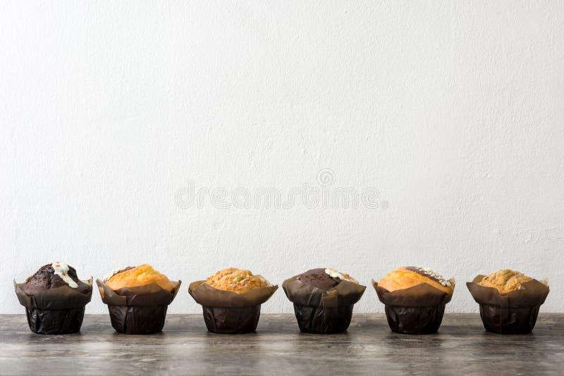 Variedade de queques em uma tabela de madeira e em uma parede branca imagens de stock