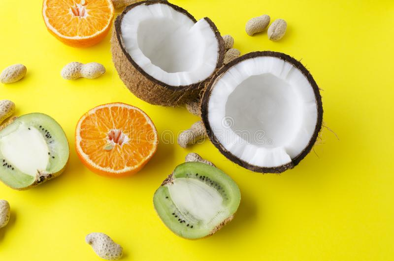 Variedade de refeição healhy no fundo amarelo Fruto de quivi, coco, laranja, amendoins foto de stock royalty free