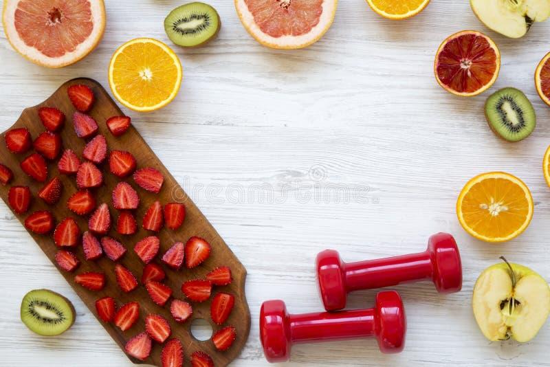Variedade de vários frutos e pesos coloridos com espaço da cópia, vista superior Conceito da aptidão, plano da dieta imagem de stock royalty free