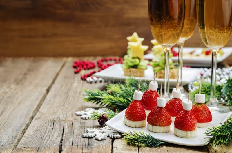 Variedade de Year& novo x27; petiscos de s e um vidro do champanhe fotos de stock royalty free