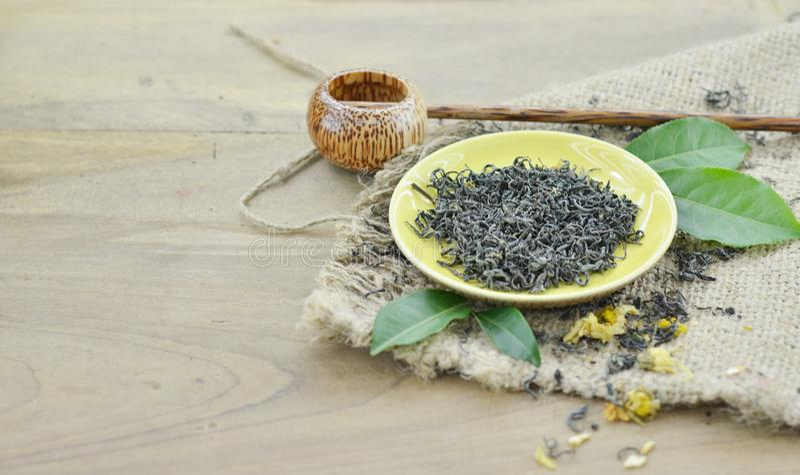 Variedade do chá seco na placa com o shaku no fundo de madeira imagem de stock royalty free