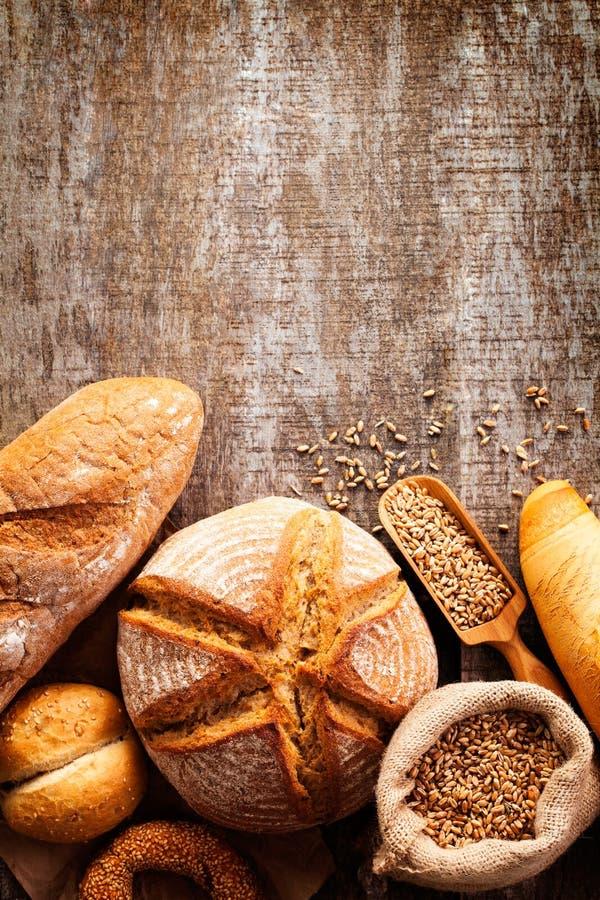 Variedade do pão cozido no fundo de madeira da tabela foto de stock royalty free