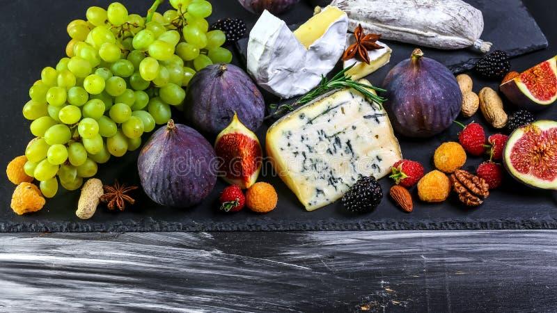 Variedade do queijo com frutos e uvas na tabela de madeira velha Vista superior Copie o espa?o fotografia de stock royalty free