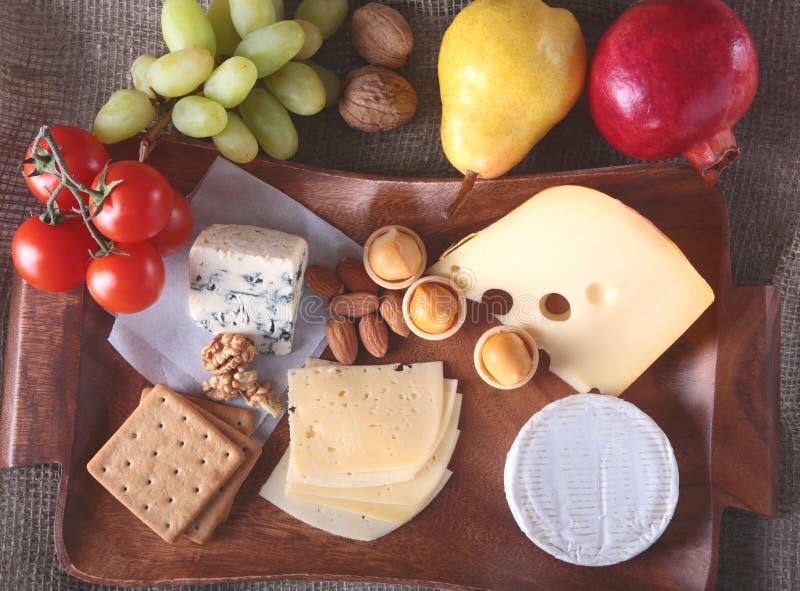 Variedade do queijo com frutos, uvas e porcas em uma bandeja de madeira do serviço foto de stock