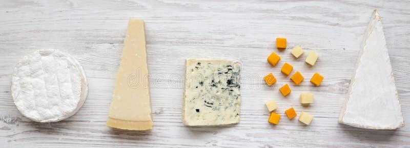 Variedade do queijo diferente em uma superfície de madeira branca, vista superior De cima de fotos de stock