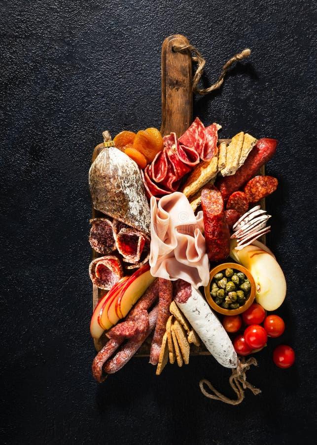 Variedade do salame e dos petiscos Salsicha Fouet, salsichas, salame, paperoni Em um fundo de madeira preto Vista superior Espa?o fotos de stock