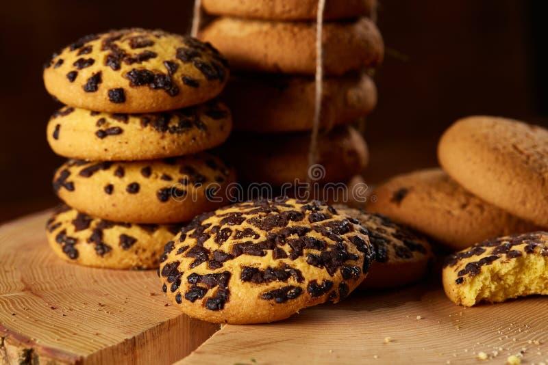 Variedade doce dos biscoitos em um log da madeira redonda sobre o fundo de madeira rústico, close-up, foco seletivo fotografia de stock