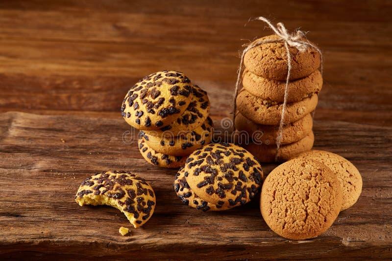 Variedade doce dos biscoitos em um log da madeira redonda sobre o fundo de madeira rústico, close-up, foco seletivo imagens de stock royalty free
