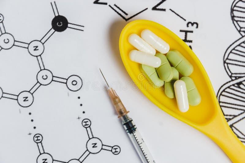 Variedade dos comprimidos, das tabuletas e das cápsulas na colher amarela, seringa no fundo branco com fórmula química imagem de stock