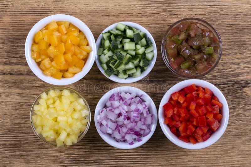 Variedade dos vegetais coloridos cortados, ascendente próximo Pimentos, tomates, pepino e cebola frescos em umas bacias Vista sup fotografia de stock royalty free