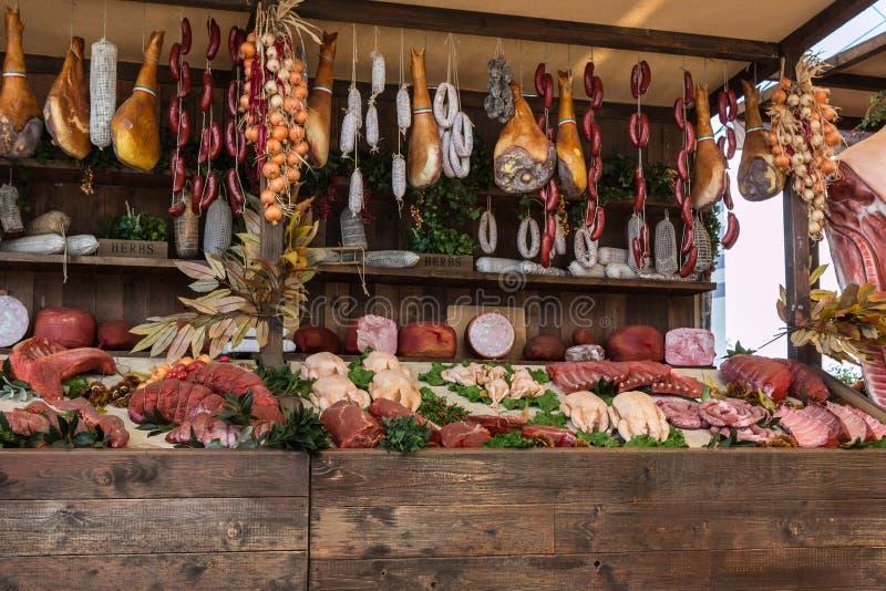 Variedade e salsichas da carne no carniceiro Shop na placa de madeira fotografia de stock