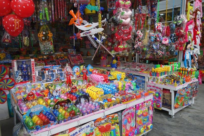 Variedade enorme de brinquedos coloridos que estão sendo vendidos em uma tenda da borda da estrada imagem de stock royalty free