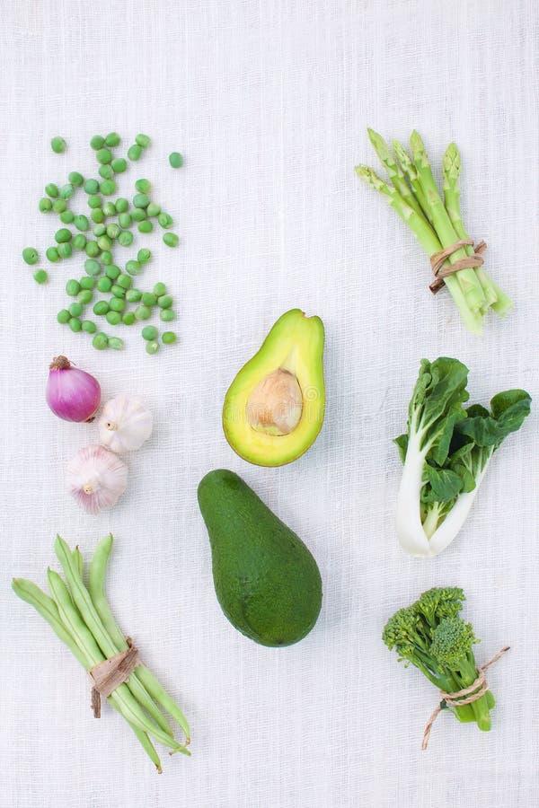 Variedade verde fresca dos vegetais no fundo branco rústico de t foto de stock
