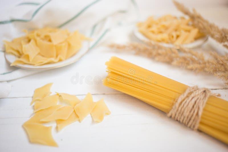 variedades de massa em uma tabela de madeira branca, espaguete, Penne, maltagliati, culinária local fotos de stock
