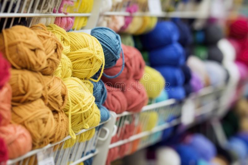 Variegated and bright pile of knitting yarn for knitting. Store of goods for creativity and needlework royalty free stock photo