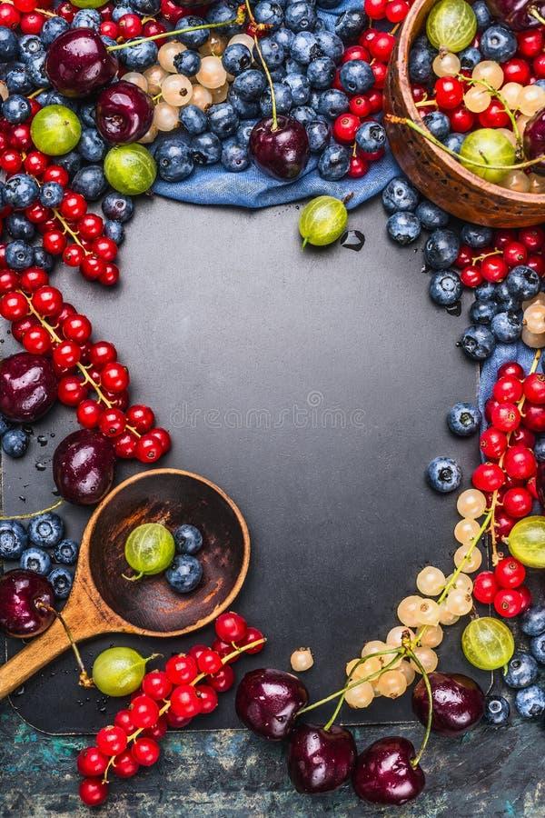 Varietà di bacche fresche di estate con il cucchiaio di cottura di legno sul fondo della lavagna, vista superiore fotografia stock libera da diritti