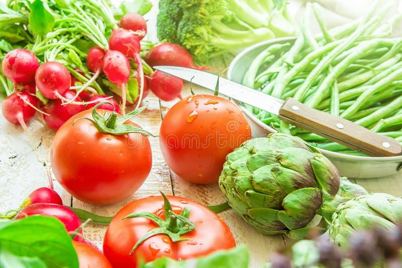 Varietà di broccoli organici freschi del ravanello rosso dei pomodori dei fagiolini dei carciofi delle verdure sul tavolo da cuci fotografia stock