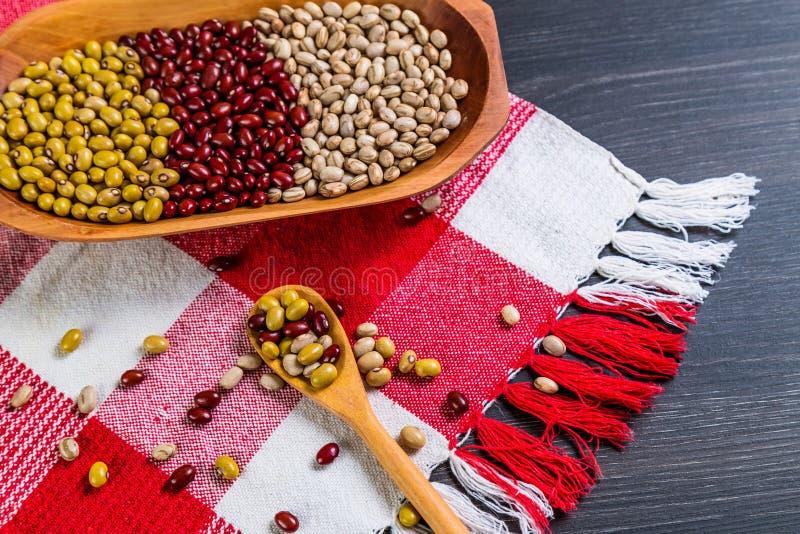 Varietà di fagioli sul cucchiaio di legno su fondo di legno fagioli verdi, arachidi, fagioli rossi e fagioli marroni fotografia stock libera da diritti