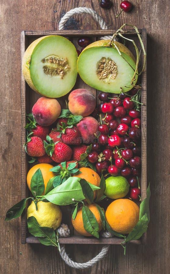 Varietà di frutta sana di estate Melone, ciliegie, pesca, fragola, arancia e limone in vassoio di legno sopra rustico fotografia stock libera da diritti