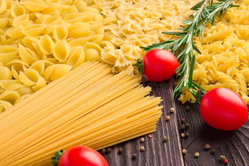 Varietà di generi e forme di maccheroni asciutti con i pomodori ed i rosmarini Alimento crudo o struttura dei maccheroni italiani immagini stock
