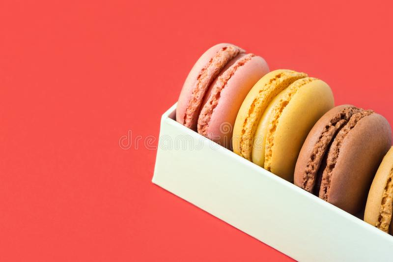 Varietà di macarons rosa della moca di giallo del caffè del cioccolato di sapori differenti multicolori in contenitore di regalo  immagine stock libera da diritti