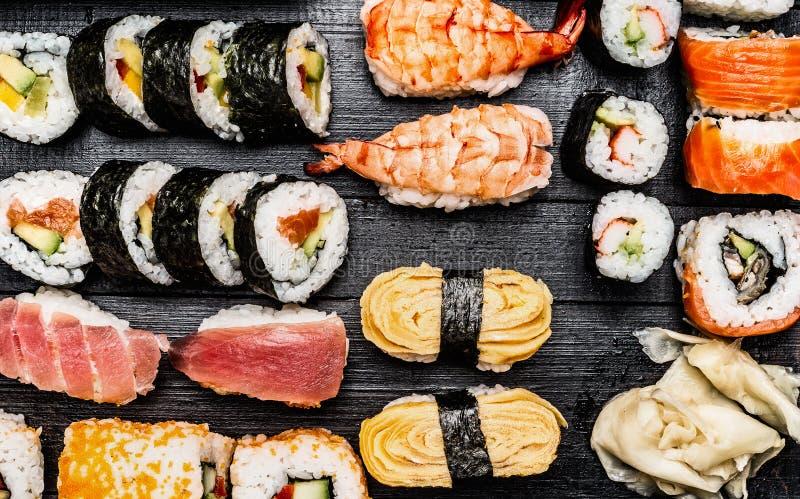 Varietà di sushi: il maki, nigiri, rotola su fondo di legno scuro fotografia stock libera da diritti