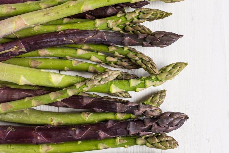 Varietà fresche dell'asparago su fondo di legno bianco immagine stock