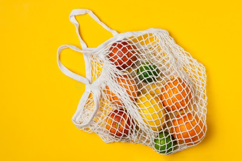 Varietà organica degli agrumi in sacchetto della spesa riutilizzabile della maglia del cotone - riciclando, stile di vita sosteni fotografia stock libera da diritti