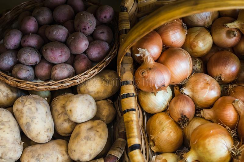 Varieties of raw potatoes and onions in baskets stock photography
